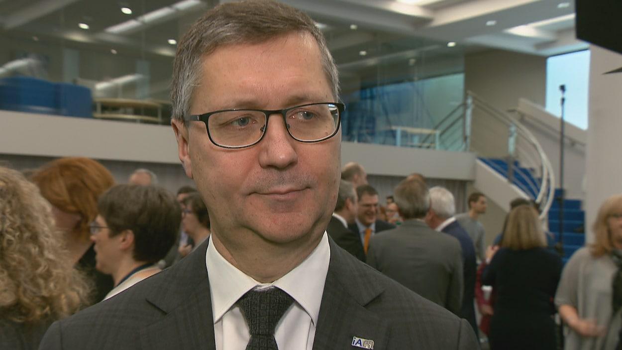 Un homme en veston et cravate et des lunettes regarde vers sa droite