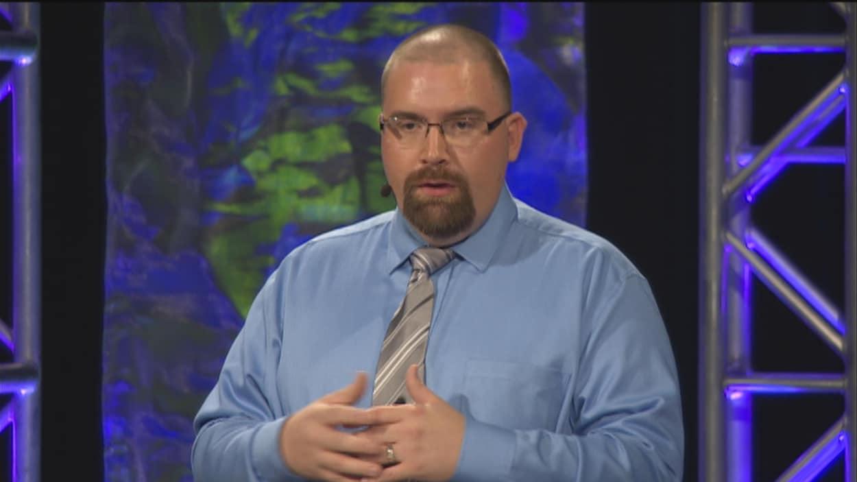 Un homme regarde droit dans la caméra et s'adresse au public.
