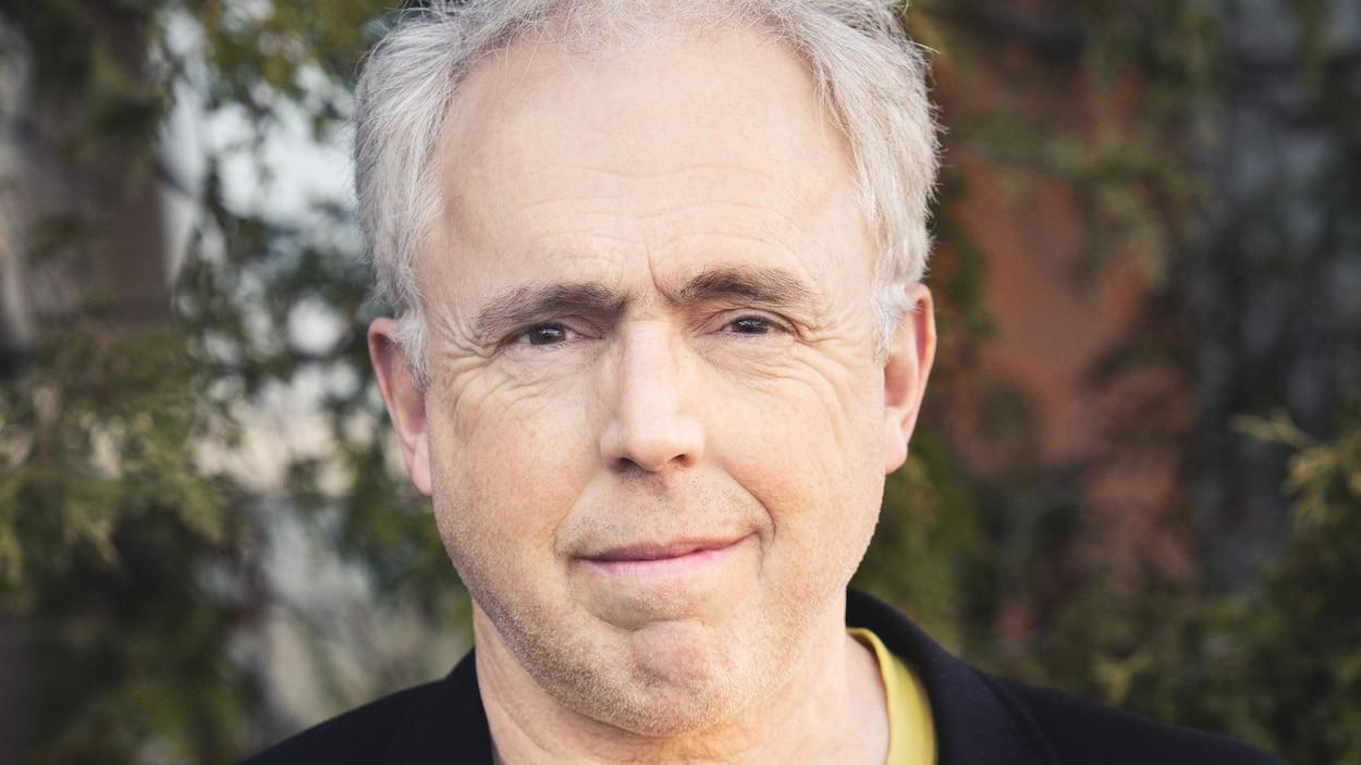 Un homme porte un veston noir et un t-shirt jaune.
