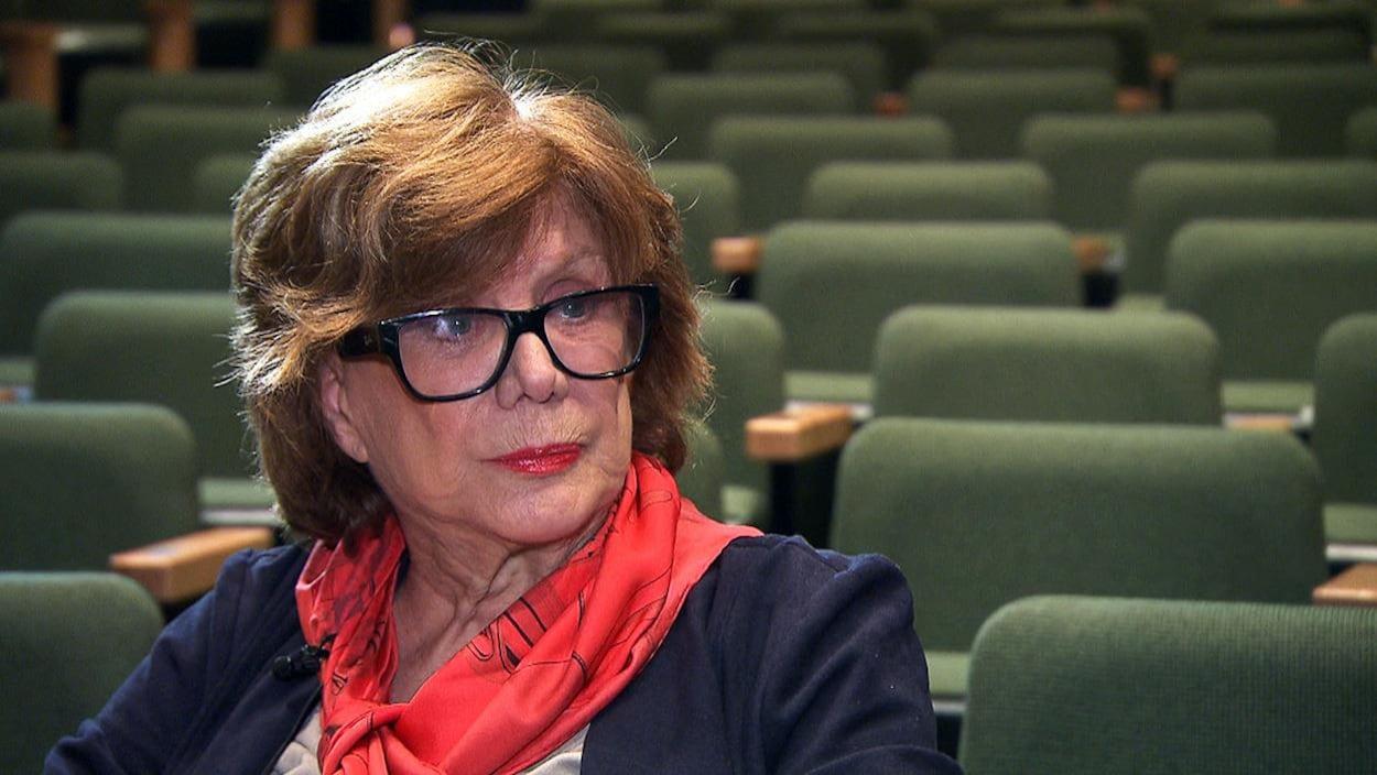 Denise Filiatrault porte des lunettes et est assise sur un banc dans une salle de théâtre vide.