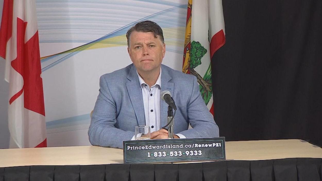 Dennis King, assis à une table devant un drapeau du Canada et un drapeau de l'Île-du-Prince-Édouard.