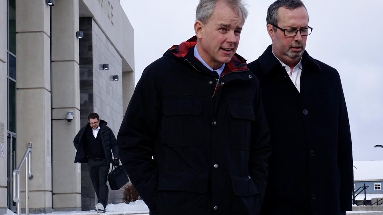 Dennis Oland qui quitte le palais de justice de Saint-Jean aux côtés de son avocat.
