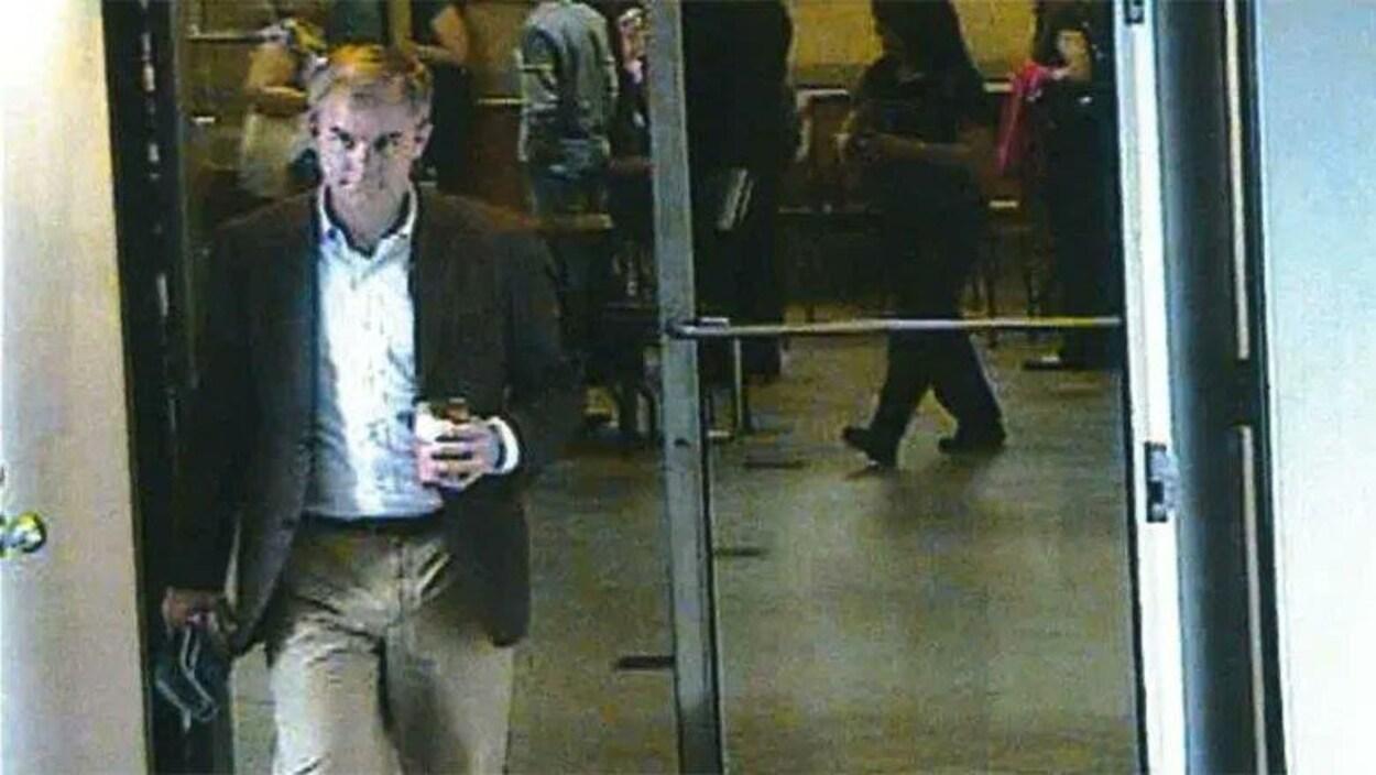 Cette image, prise d'une vidéo de surveillance, montre Dennis Oland portant des pantalons beiges et un veston foncé, le soir où son père aurait été tué.