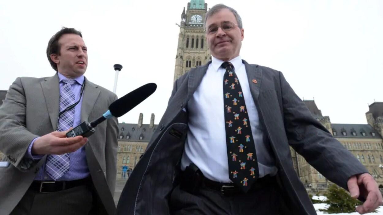 Un reporter tend un micro vers le sénateur Dennis Patterson qui marche devant le Parlement à Ottawa.