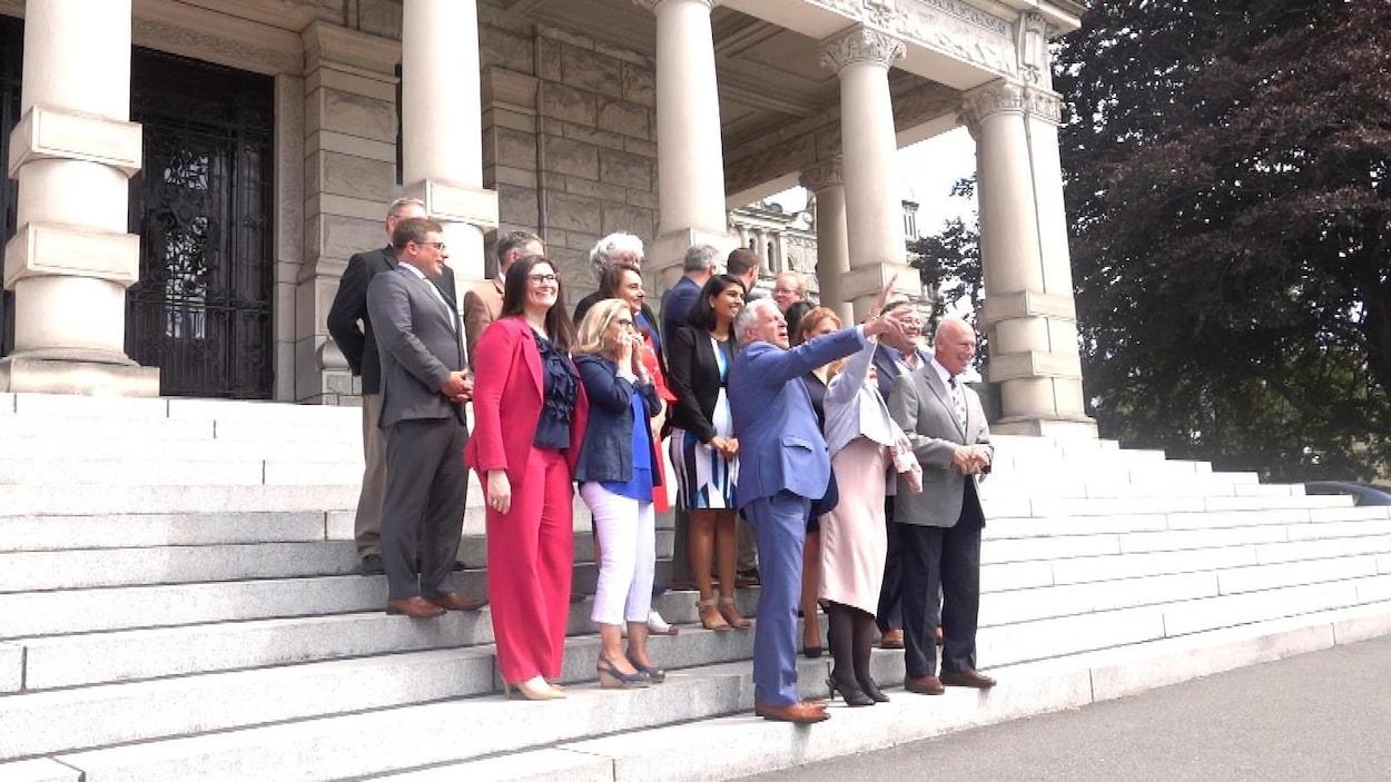 Un groupe de personnes qui posent devant un édifice.