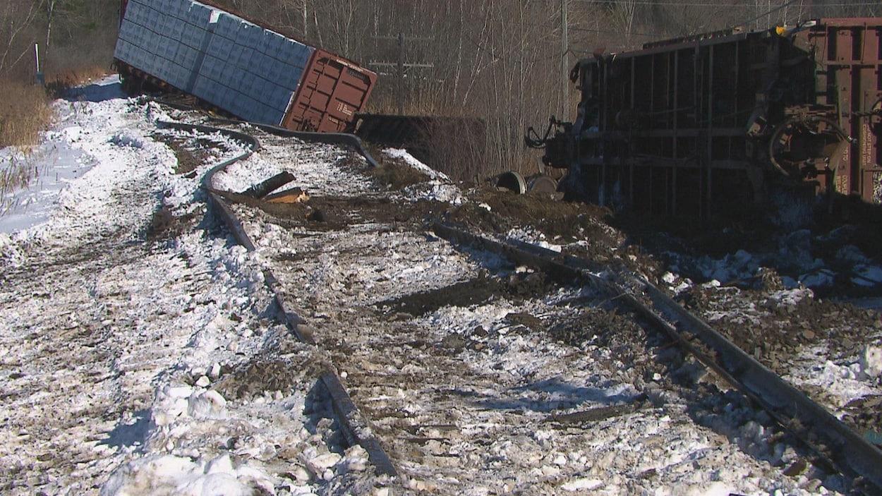 Deux wagons sont détachés l'un de l'autre et sont renversés sur le côté. Les rails sont arrachés et déviés de leur trajectoire.