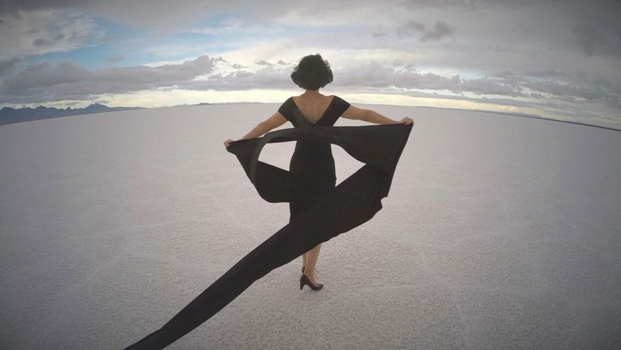 Une femme portant une robe à volants et des escarpins noirs marche dans le désert.