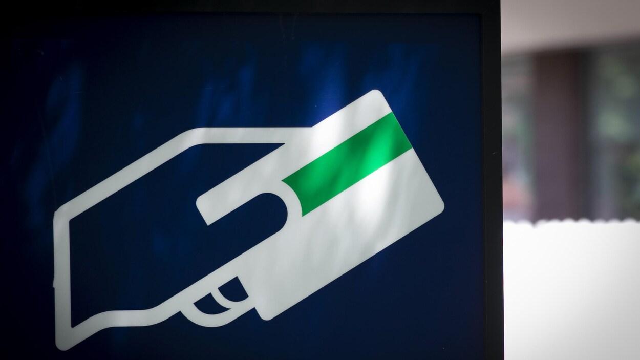 Symbole montrant une main qui tient une carte d'accès à un guichet.