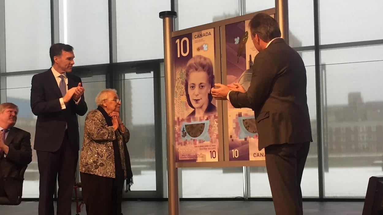 Des dignitaires entourent une grande affiche illustrant le nouveau billet de banque de 10 $.