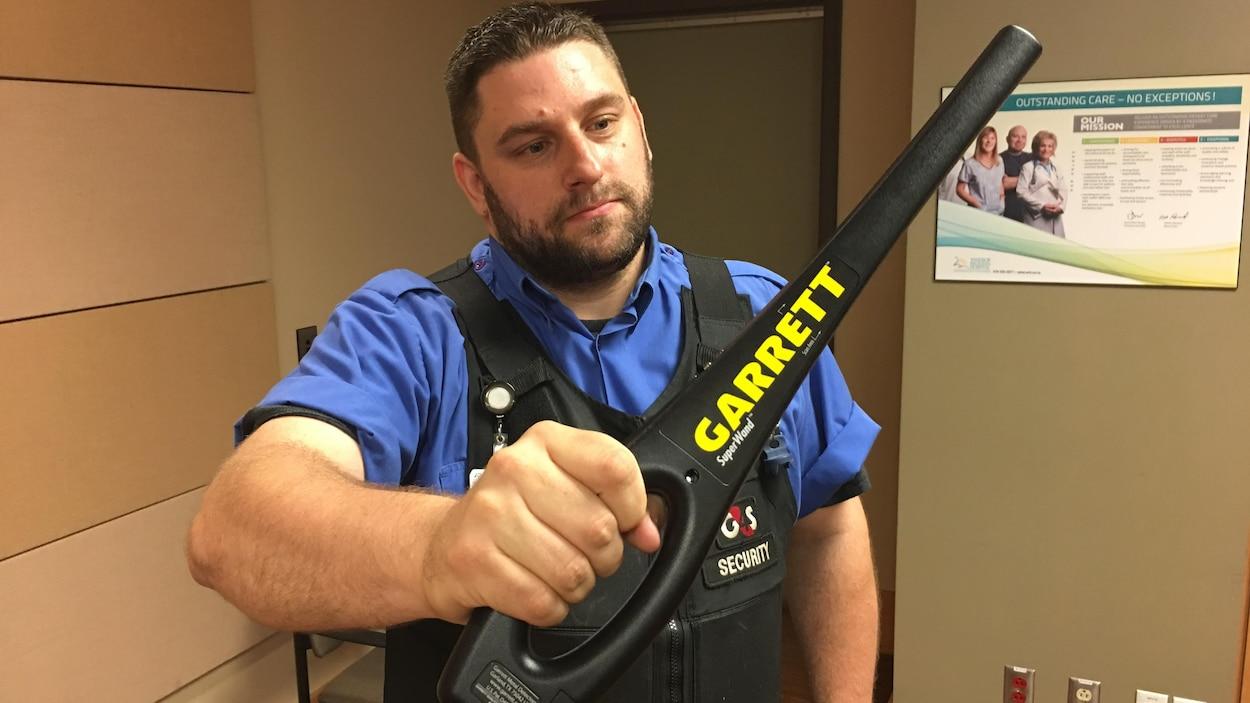 Un gardien de sécurité montre un détecteur de métaux manuel