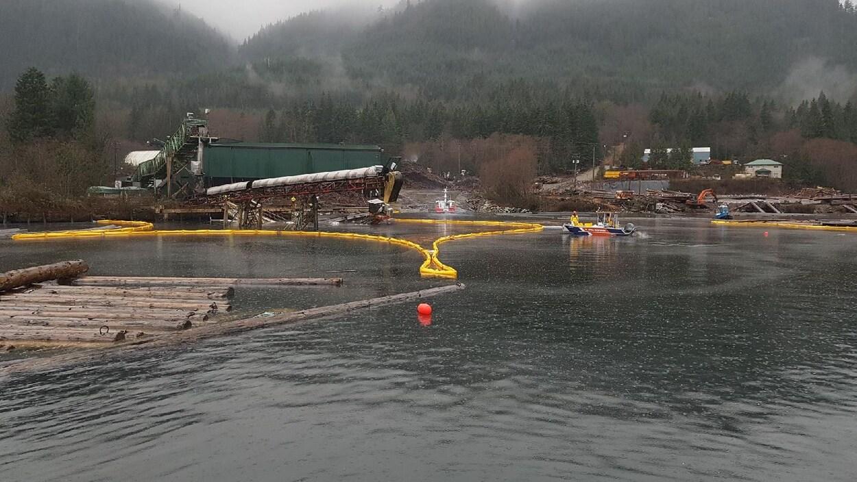 Un déversement diésel entouré d'un barrage jaune sur la surface de l'eau.