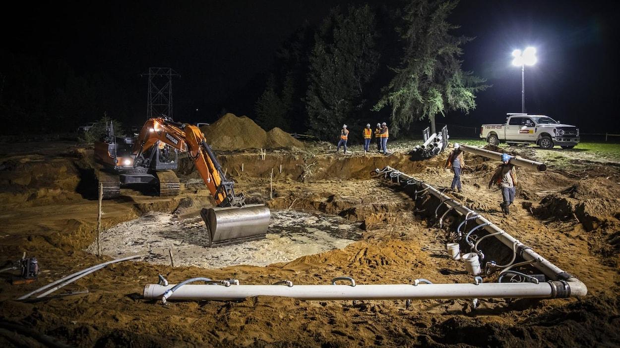 Un chantier avec des travailleurs, de nuit.