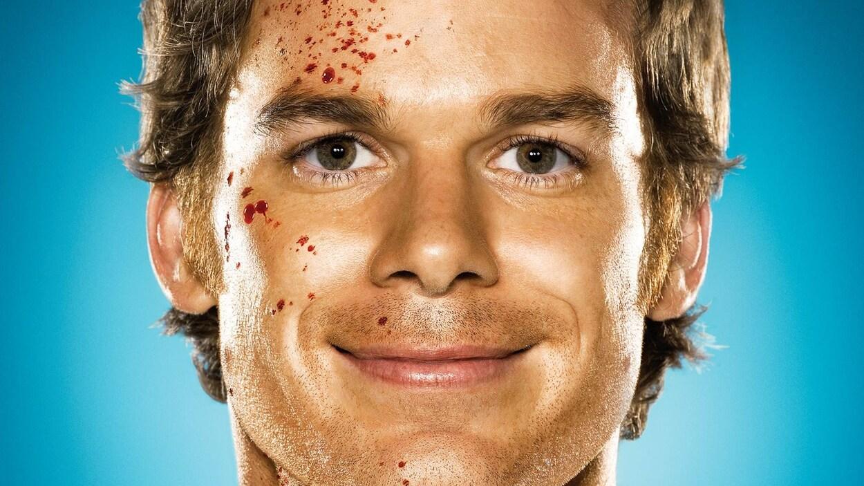 Un homme avec des éclaboussures de sang dans le visage sourit.