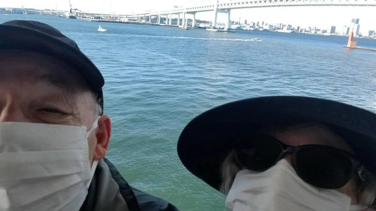 Un couple portant des masques sur la bouche et le nez se prennent en photo sur le pont d'un bateau de croisière.