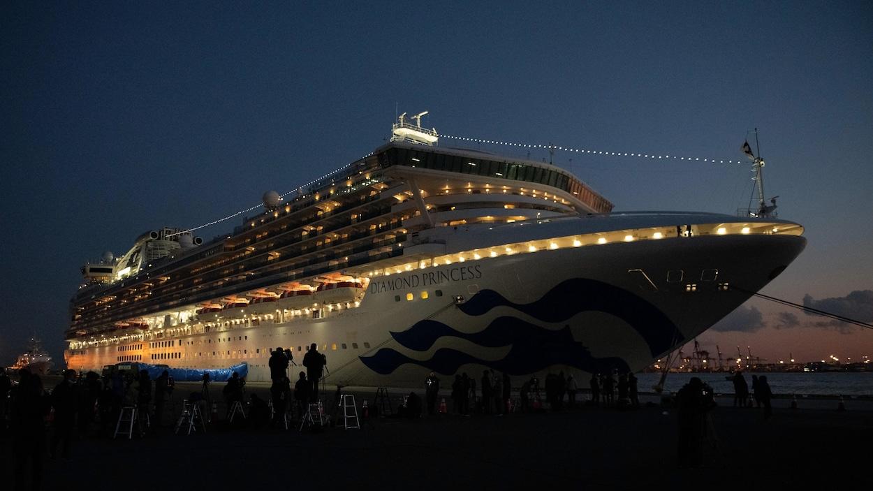 Plusieurs caméramans et photographes sont devant le navire, éclairé, la nuit.
