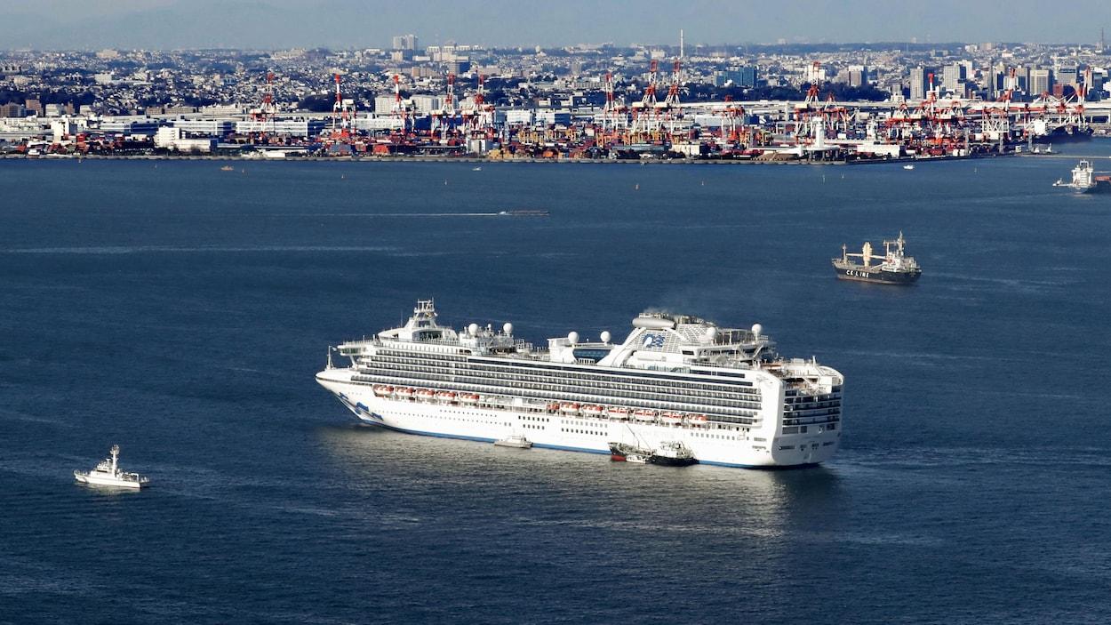 Un gros paquebot est à quelques centaines de mètres d'un port.