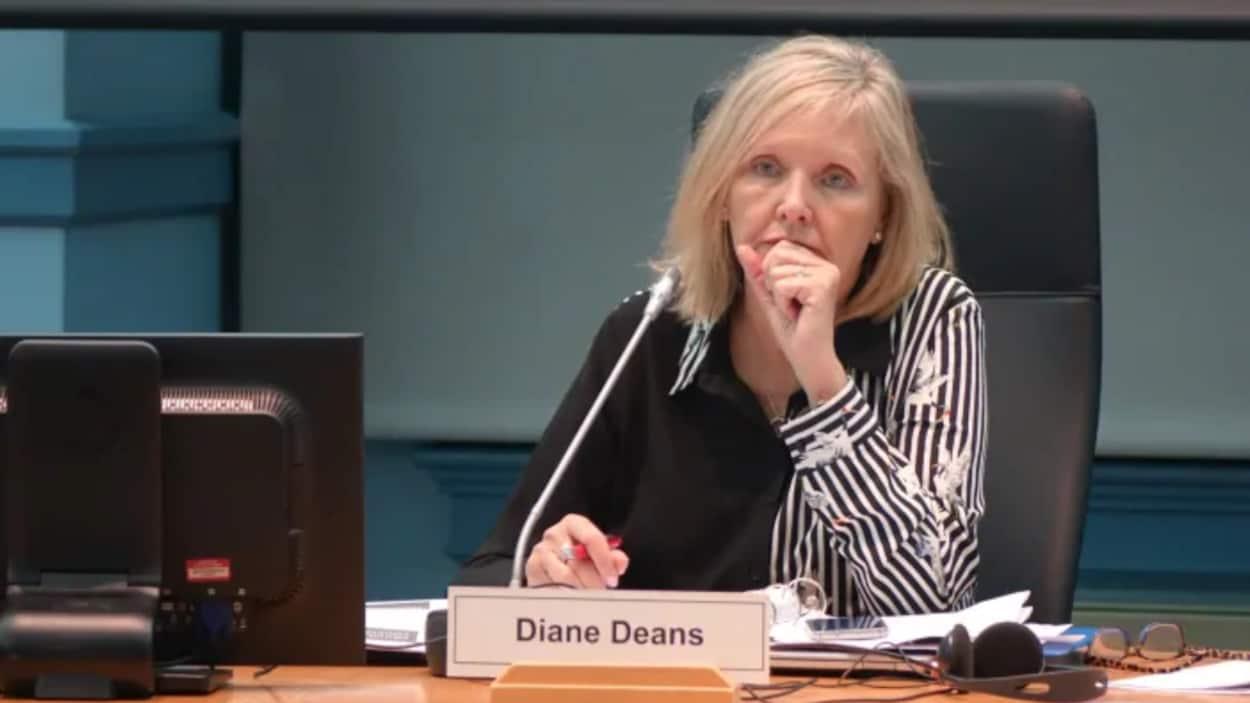 Une femme assise à un bureau devant un micro.