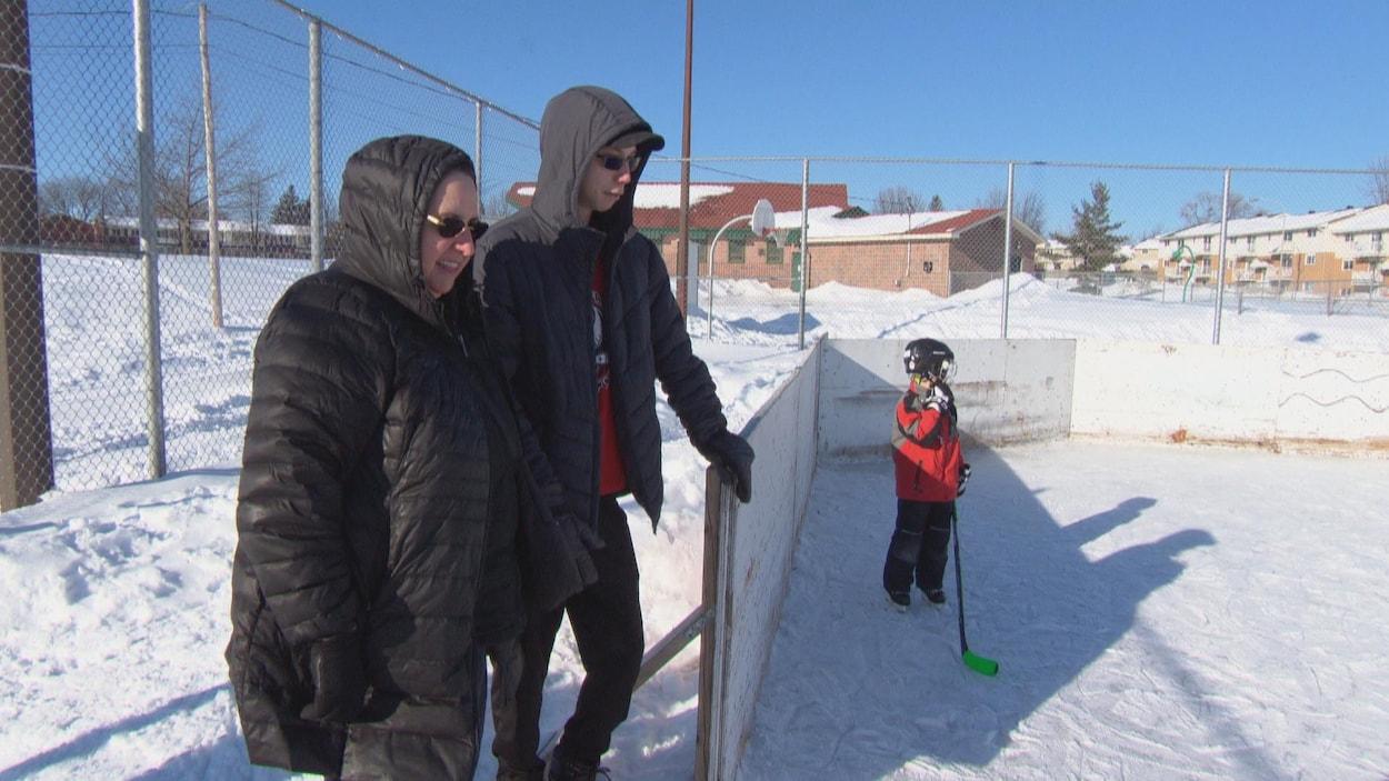 Diane et William Allard  sont debout près de la bande de la patinoire extérieure. Un jeune garçon patine.