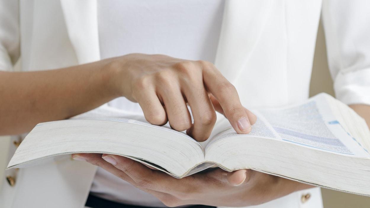 Une personne fait une recherche dans une dictionnaire.