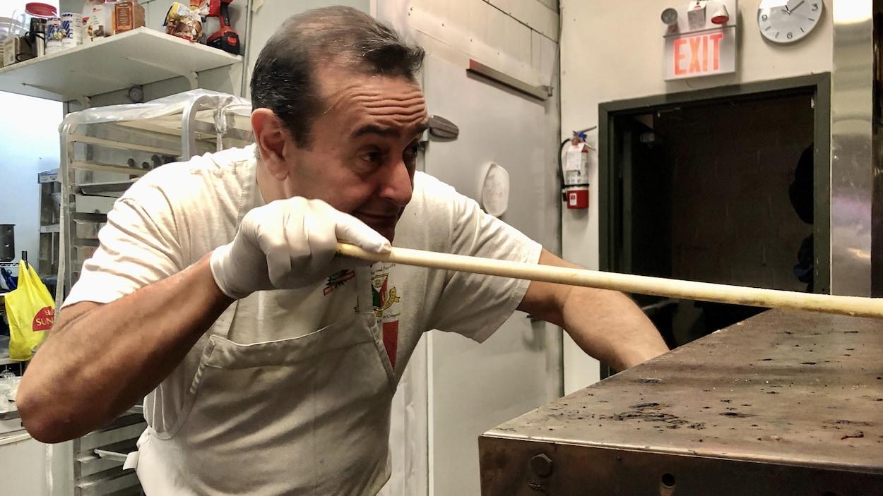 Didier, devant son four à pizza, poussant sa pelle à pizza.