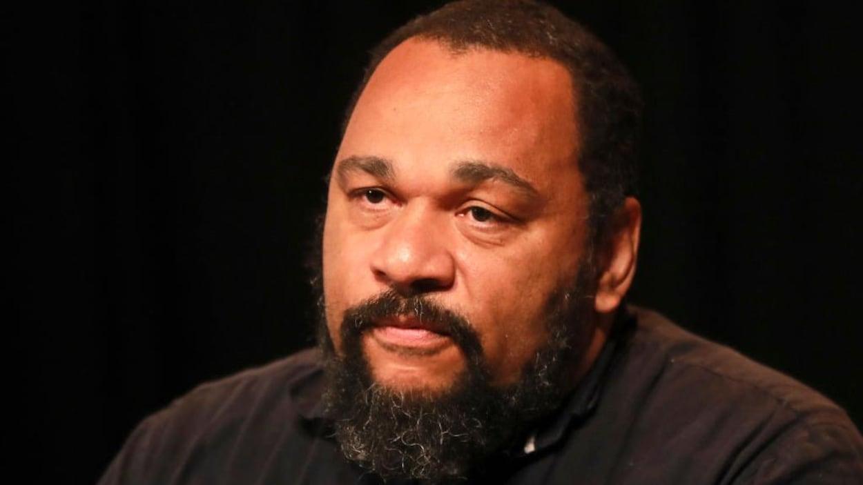 Portrait de Dieudonné portant une chemise noire et une barbe.