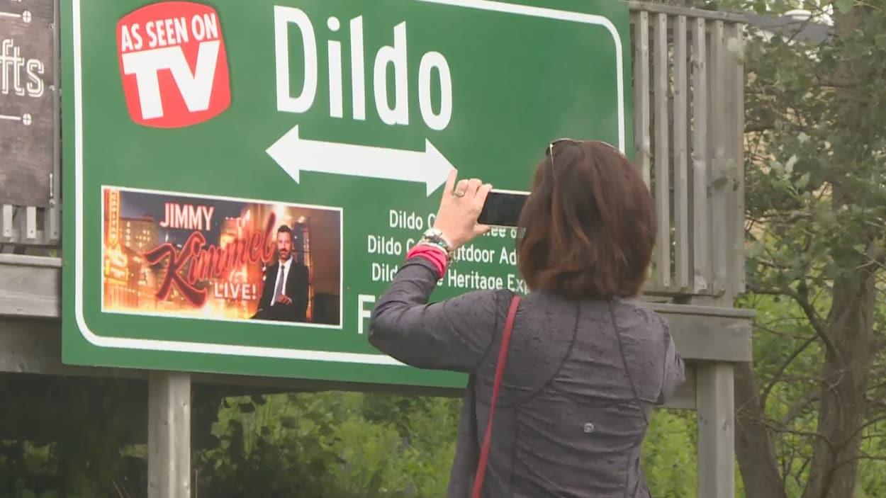 Une femme prend une photo d'une affiche indiquant le nom du village.