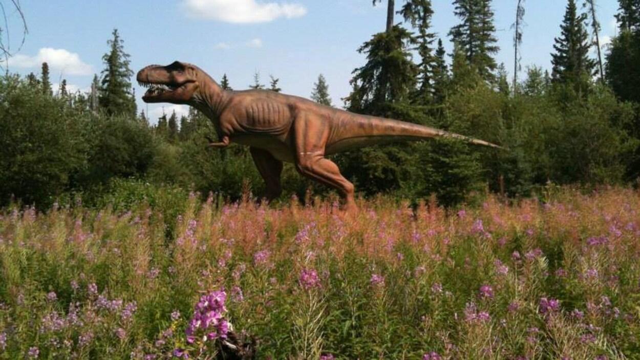 Par une journée d'été, un faux tyrannosaure rex se promène dans une clairière parsemée de fleurs bordée par des arbres.