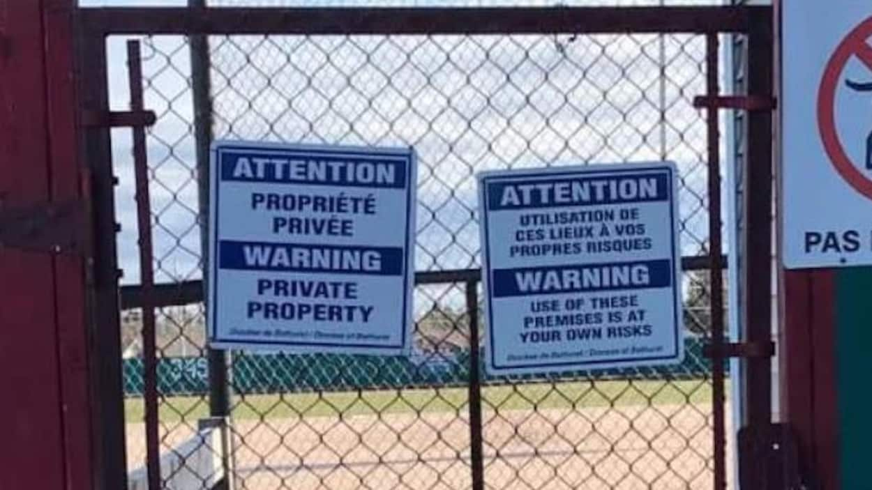 On voit des affiches d'interdiction de passage sur un terrain de baseball public.