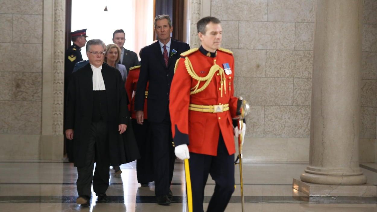 Un agent de la GRC en rouge escorte les dignitaires dans un corridor en marbre du Palais législatif du Manitoba.