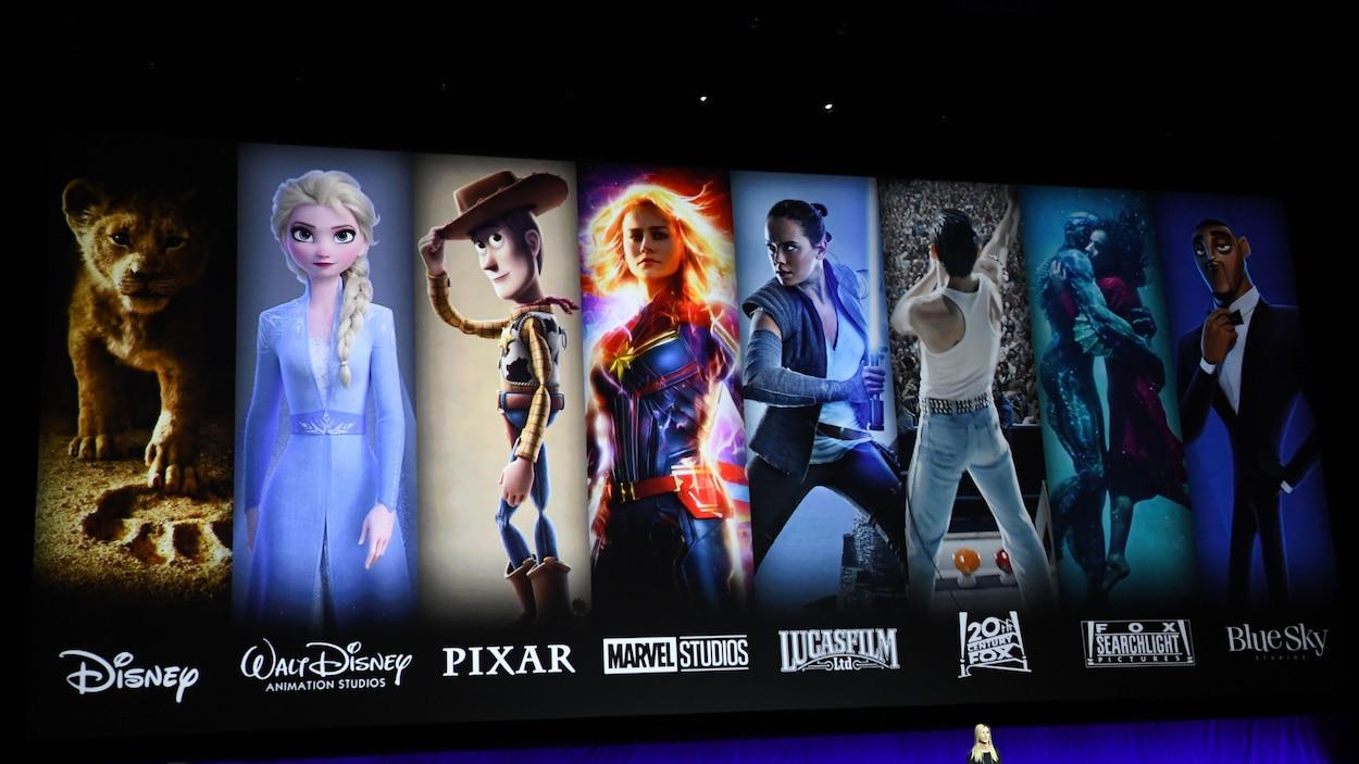 Une femme se tient debout devant un très grand écran sur lequel sont présentées les différentes filiales de Disney avec des personnages iconiques qui y sont associés