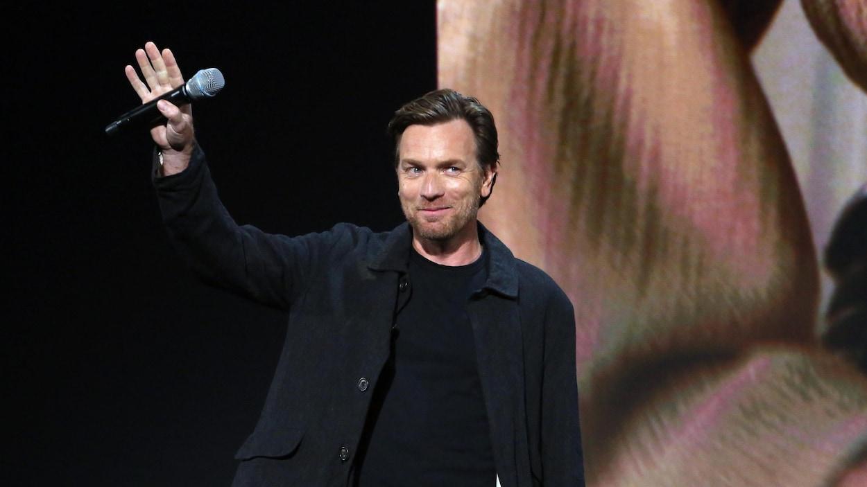 Un homme vêtu de noir sur une scène tient un micro dans la main alors qu'il adresse un salut à un auditoire.