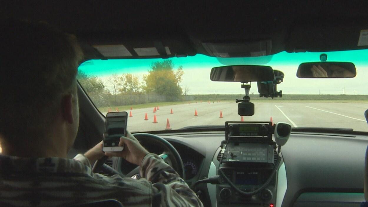 Un homme conduit avec un téléphone cellulaire à la main. Sur la route devant sa voiture, il y a des cônes orange.