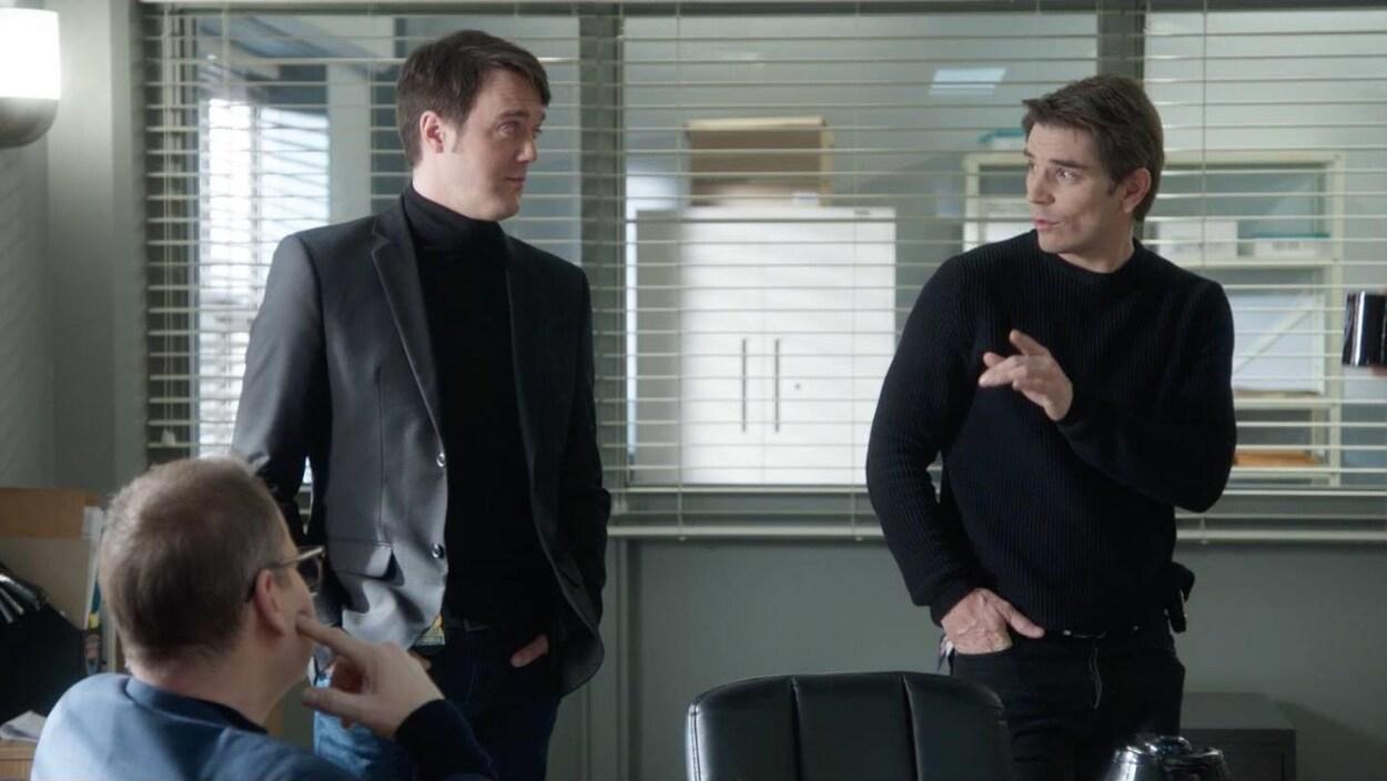 Trois hommes sont ensemble, deux se parlent.