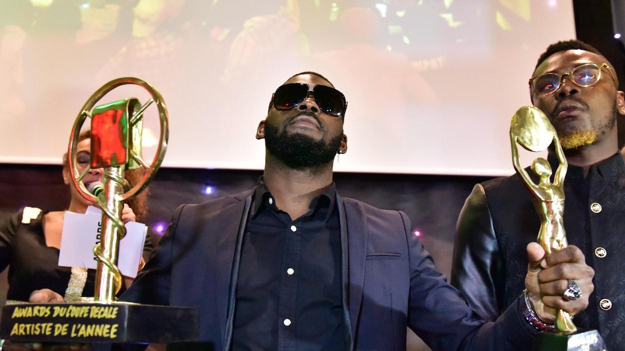 L'homme porte des lunettes noires et pose avec un trophée dans chaque main.