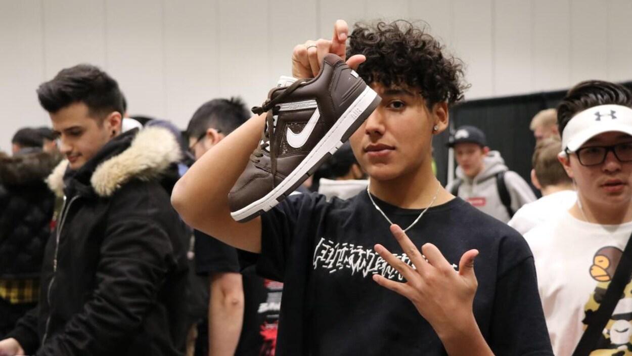 Un homme de 23 ans tient dans sa main droite une des chaussures qu'il essaye de vendre pendant que d'autres jeunes marchent près de lui.