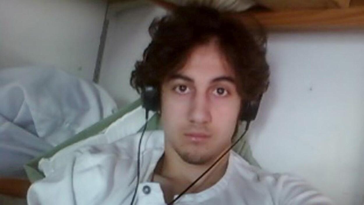 Djokhar Tsarnaev fixe la caméra avec des écouteurs sur les oreilles.