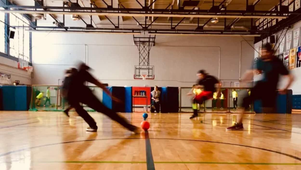 Des gens jouent au ballon-chasseur dans un gymnase.