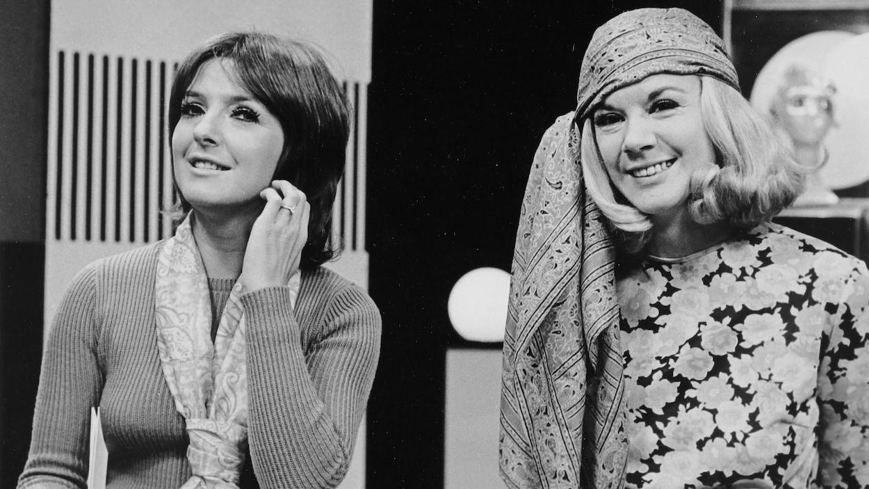 Dominique Michel et Denise Filiatrault posant côte à côte avec de longs foulards noués au coup et à la tête.