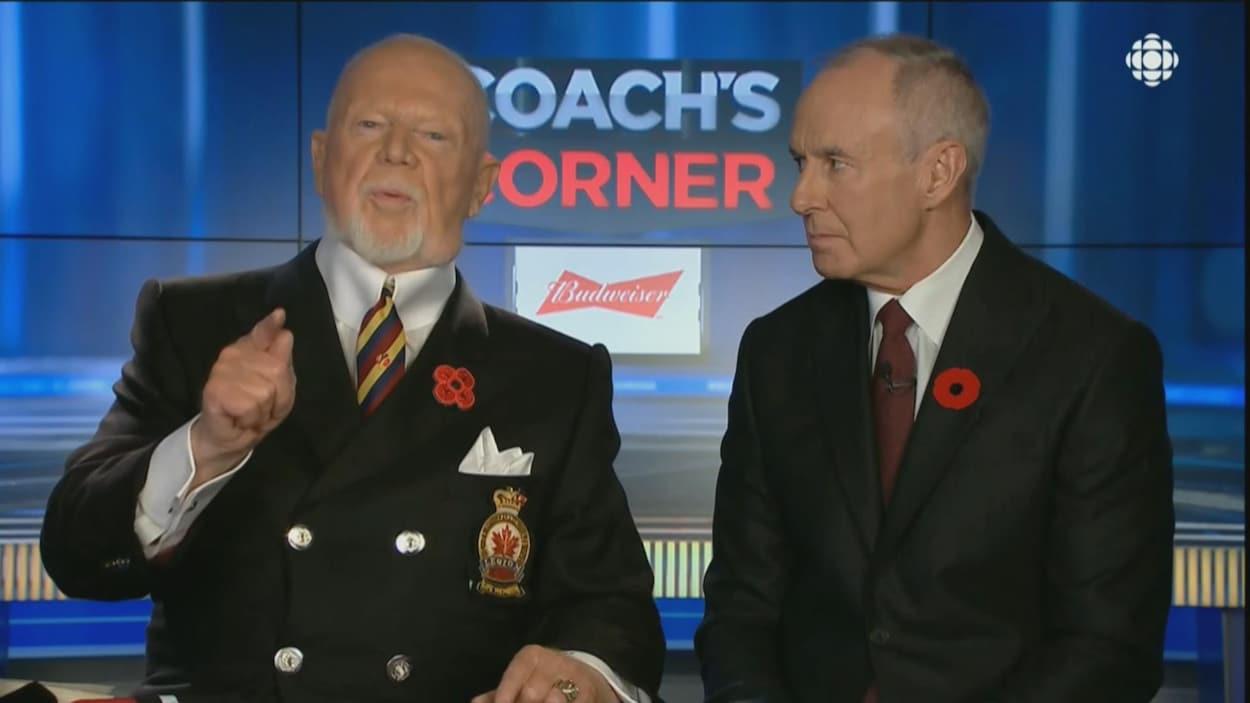 Deux hommes discutent lors d'une chronique à la télévision.