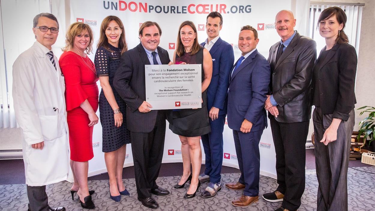 Des hommes et des femmes en costumes, en robes et en habits de médecin sourient. Un homme et un femme au milieu tiennent une plaque remerciant la Fondation Molson pour son don.