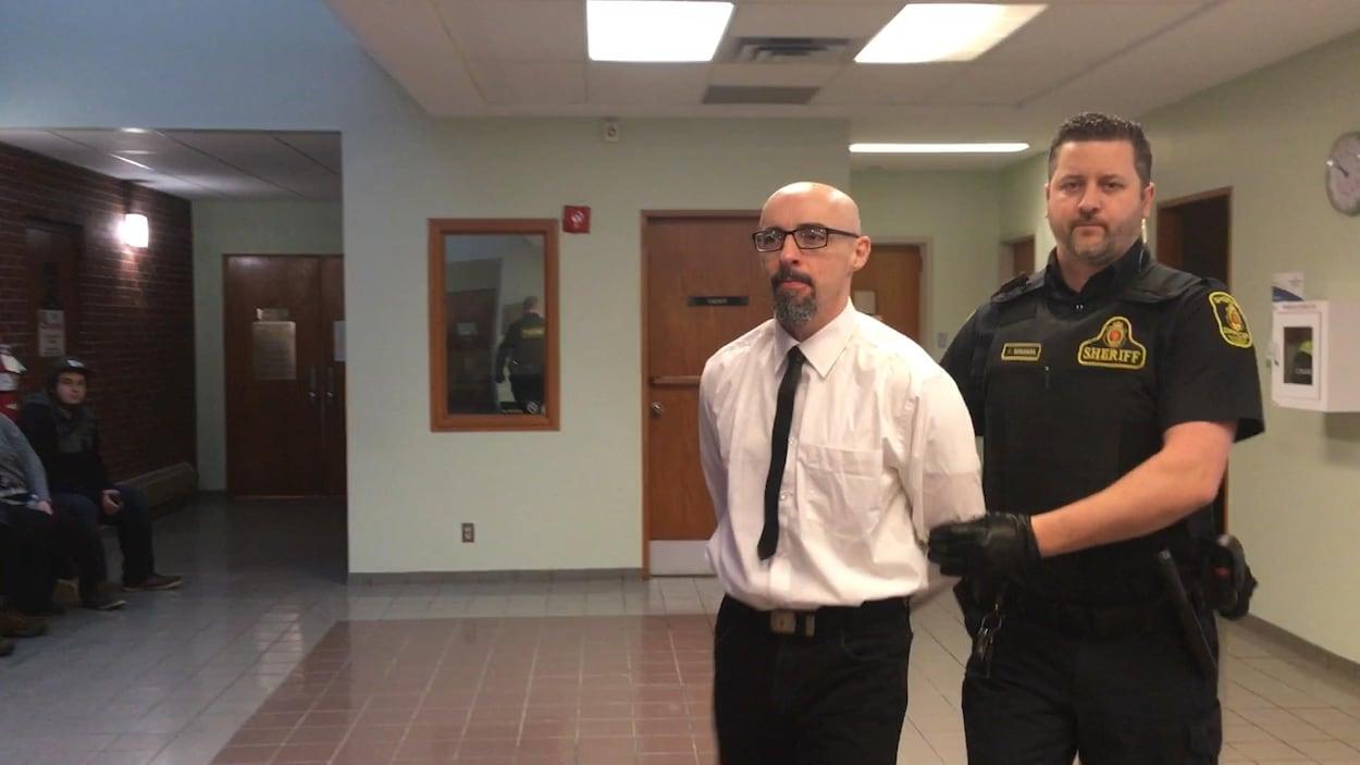 Donald MacHaight menotté avec un agent de police derrière lui.