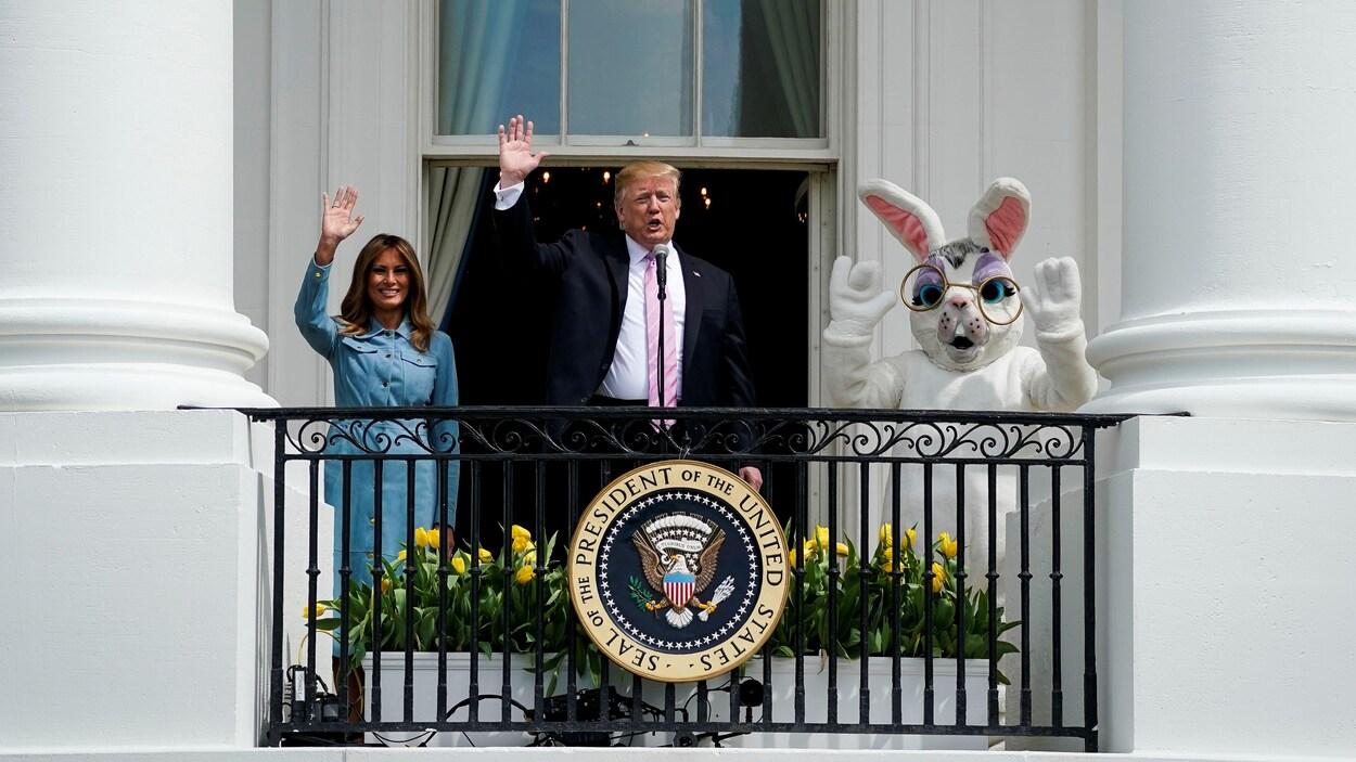 Le couple présidentiel, accompagné d'un individu portant un costume de lapin, salue vers la caméra.