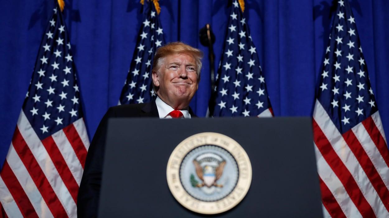 Donald Trump devant des drapeaux américains