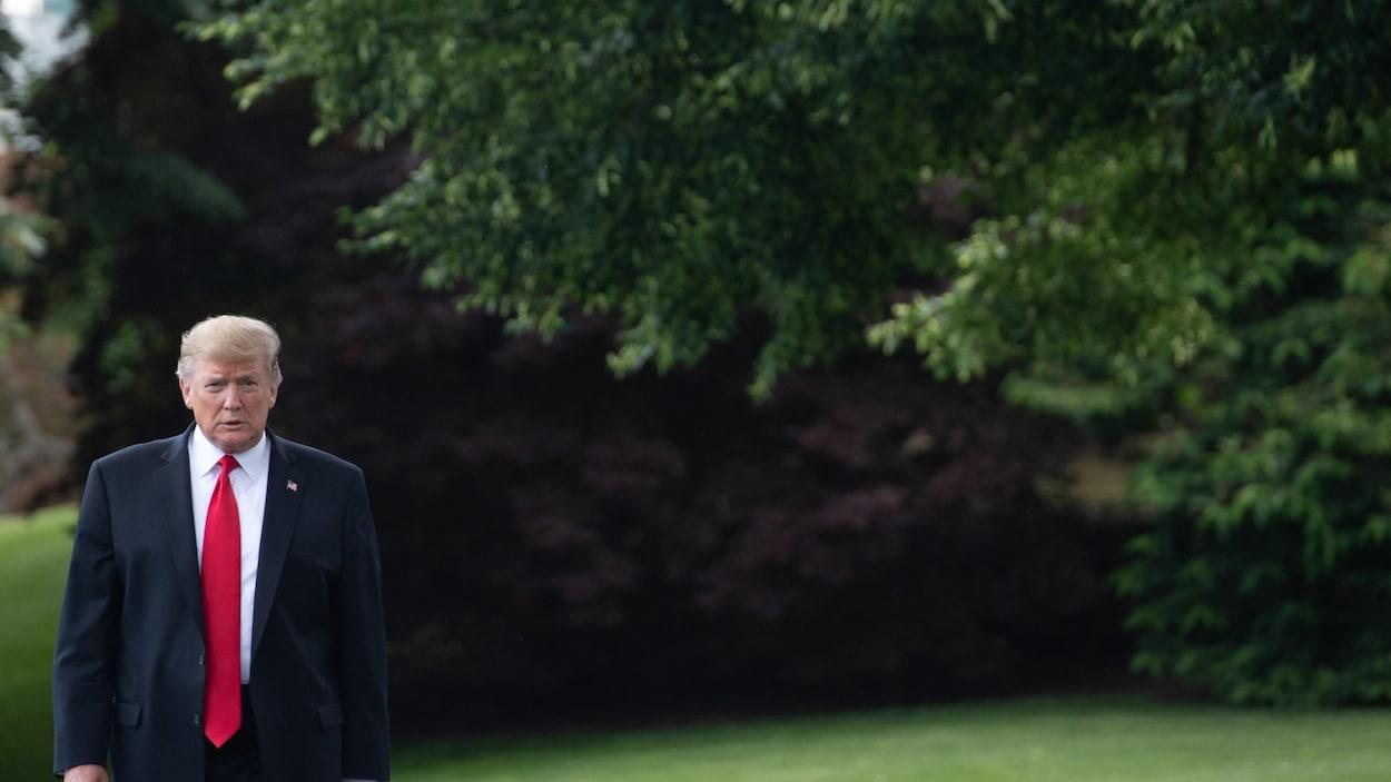 Donald Trump, portant un complet et une cravate, marche dans un jardin de la Maison-Blanche.
