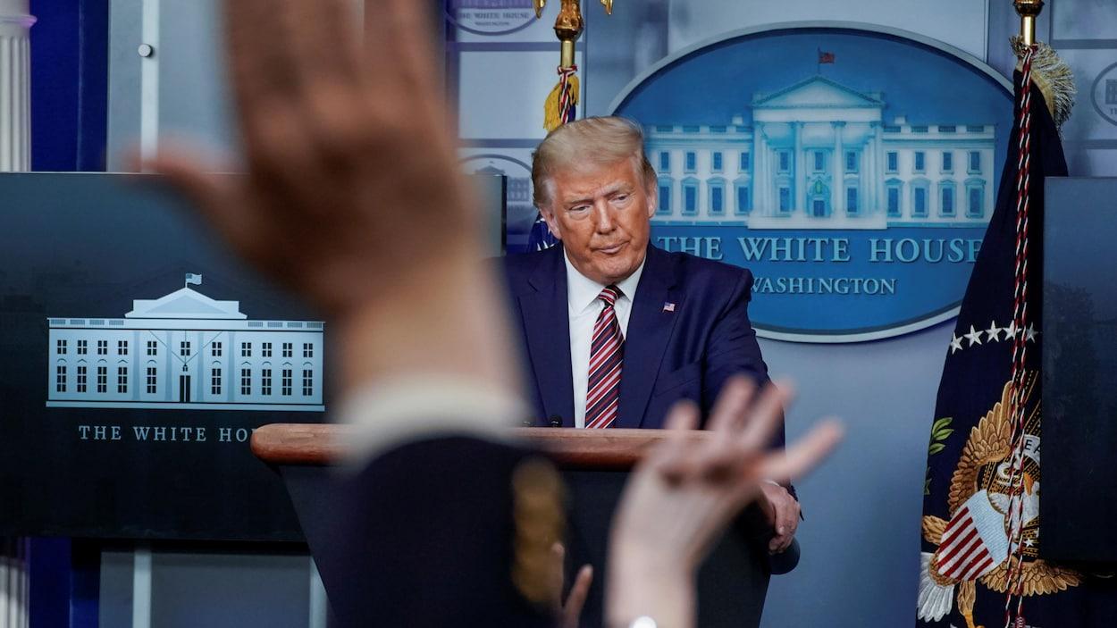 De nombreuses mains sont levées pour poser une question au président.