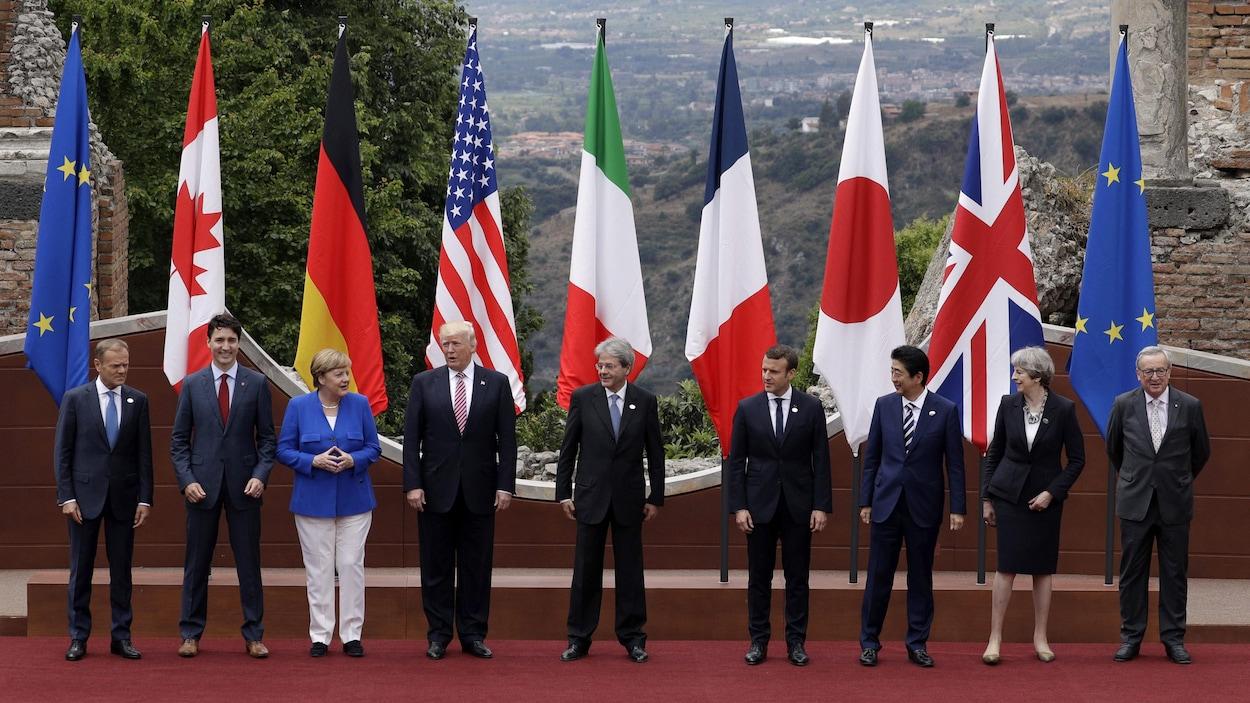 Les dirigeants du G7 sont réunis à Taormine en Italie. Ils forment une ligne droite, l'un à côté de l'autre. Ils sont sur un tapis rouge, tous devant les drapeaux de leur pays respectif.