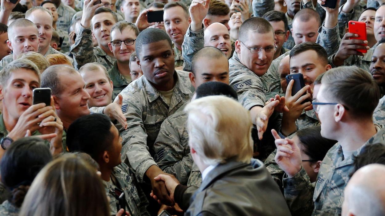 Donald Trump, qui est entouré de dizaines de militaires, serre la main de l'un d'entre eux, tandis que d'autres lui tendent la main.
