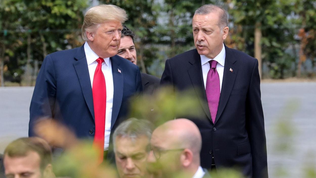 Deux hommes en complets discutent.