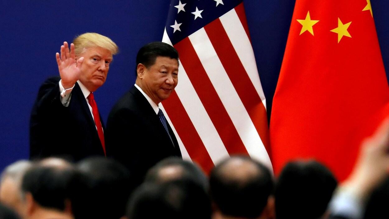 Donald Trump, qui lève la main en guise de salutation, et Xi Jinping marche sur une scène devant une foule. Derrière sont accrochés les drapeaux des États-Unis et de la Chine.