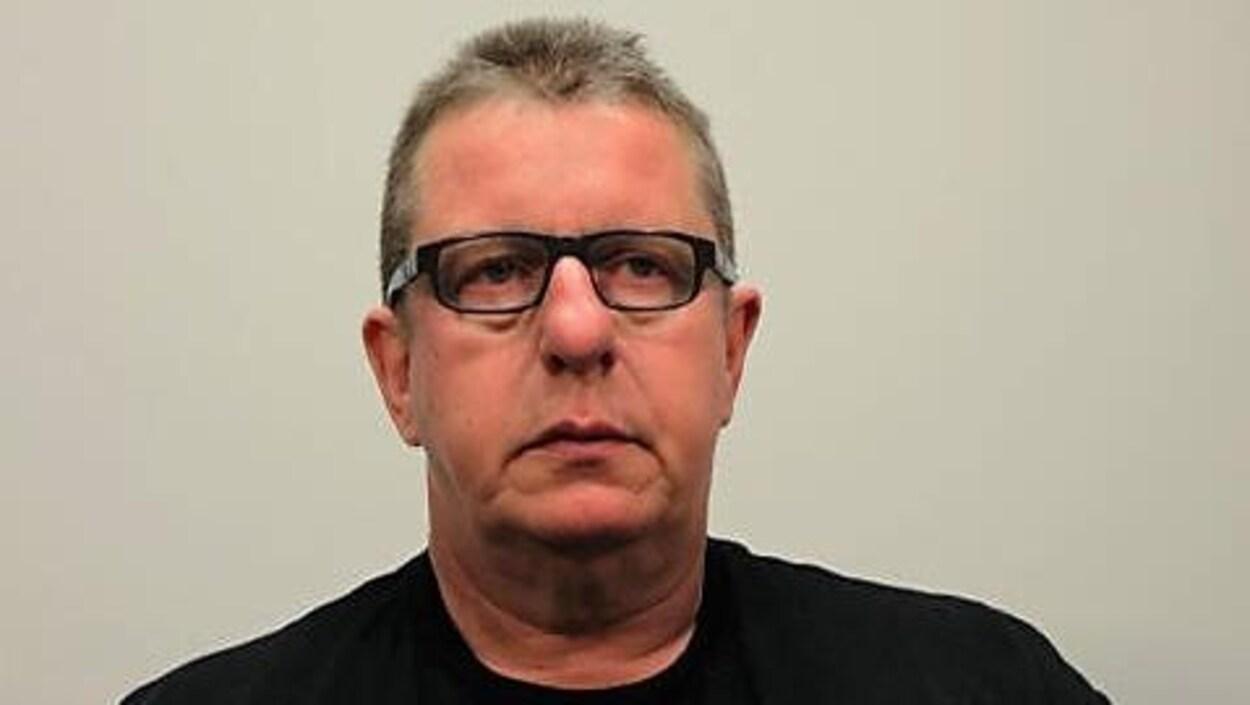 Photo de l'accusé, Donatien Beaulieu. Il porte un chandail noir et des lunettes. Il a les cheveux grisonnants coupés courts.
